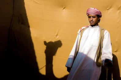 Portrait of a camel handler in the shadow of his animal before the starting line. Many are hailing from South Asia and Africa.