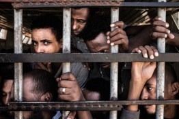 Detained migrants from Eritrea gather at the barred entrance to their cell in a detention center near Gharyan, Libya, April 15, 2014. Many of the men say that the Italian Coast Guard intercepted them as they tried to illegally cross the Mediterranean from Libya towards Italy. They say, the Coats Guard put them on a cargo vessel and told them that they would be taken to Italy, but the vessel took them back to Tripoli, Libya. After the revolution, Libya has become the major launching point for irregular migrants to cross the Mediterranean. In the first three month of 2014, the Italian Coast Guard intercepted 15,000 people on the Mediterranean, compared to 750 in the same time last year.