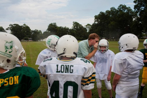 A coach whispers a play to a pee wee football player during a practice in Greenwood, Mississippi on August 2, 2012. Football is a big part of life and culture in the Mississippi Delta.