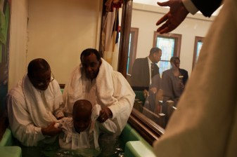 Reverend Calvin Collins and Charles McCoy help baptize a young boy during a service in Greenwood, Mississippi on Super Bowl Sunday, February 2, 2014.