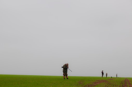 From the new book A Place in the Country. Holkham Estate. North Norfolk. Pheasant and Partridge shoot. A 'Rough' Day. Guns wait in a field under a pale sky.