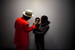 Defendant with his son and his ex partner in the building's corridor where he lives. Bed Stuy, Brooklyn, NYC, 2013