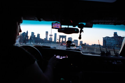 bounty hunter, drives across Brooklyn Bridge at dusk. NYC, 2012.