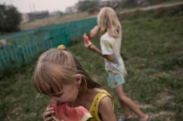 (Eng) In short Russian summers, life takes place completely outside. (ITA) Due bambine fanno merenda con un cocomero in giardino.