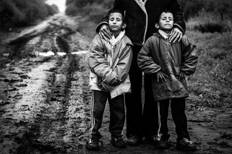 12-1- 2014. Roque Sáenz Peña, Province of Chaco. Twins Aldo and Maximiliano Barrios (2004) and their mother Elena Alderete (1977) posing on their home street. Both children suffer from a severe condition, congenital microcephaly, one of the illnesses associated with the use of neurotoxic substances in transgenic agriculture. The Barrios twins attend one of the many facilities for the disabled that increase in number considerably year after year.
