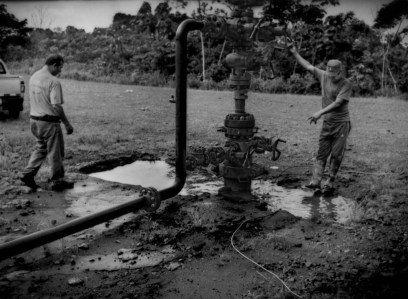 """""""Afectado (affected person): Water, highly contaminated by petroleum waste, gathers around a slurry-waste injection compressor inspected by Jose Aveiga, the landowner. The slurry-waste injection compressor is supposed to safely return waste petroleum slurry safely thousands of meters back into the earth from where the petroleum came at this exhausted well, but it leaks petroleum waste into the environment, where it has soaked into the water table. Cattle manure can be found around this pit because the cattle drink the contaminated water. In turn, the family consumes the beef and dairy products from their herd. Via Auca near the Rio Tiputini, Ecuador. The oil company paid Aveiga US$12/year to occupy this hilltop on his 80 hectare farm. Via Auca near the Rio Tiputini, Ecuador."""
