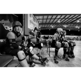Day 3: Roller Derby League night in Newcastle. From left Tootsie Turbo Zoom, Baroness Von Brutal, Chopper Weed and Red Hot Riot of the Maitland Roller Girls watch on from the line-up bench. The entire team are all Maitland girls who are a new league that started only a year ago in the comp, in the beginning some of them even had to learn to skate! Quick learners with loads of determination they won their bout 178 to 135 tonight against the Coastal Knockouts.