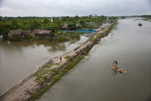 A man steers his banana raft through the flood-affected village in Satkhira.