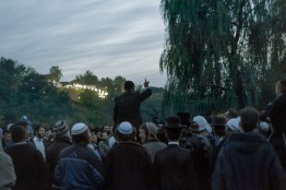 Pilgrims sing and dance near a lake. Approximately 30,000 religious Jews make an annual pilgrimage to the tomb of Breslover Rabbi Nachman's tomb in Uman, Ukraine for Rosh Hashanah. The pilgrimage is unique because it attracts men from across the spectrum of Judaism. In making the pilgrimage, they believe that Rabbi Nachman will intercede on their behalf on Yom Kippur, the Jewish day of atonement.