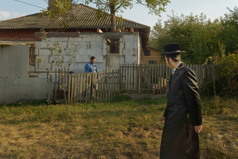 A pilgrim and local inspect each other. There is little interaction between locals and pilgrims. Approximately 30,000 religious Jews make an annual pilgrimage to the tomb of Breslover Rabbi Nachman's tomb in Uman, Ukraine for Rosh Hashanah. The pilgrimage is unique because it attracts men from across the spectrum of Judaism. In making the pilgrimage, they believe that Rabbi Nachman will intercede on their behalf on Yom Kippur, the Jewish day of atonement.