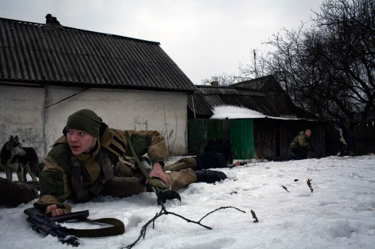 A pro Russia rebel docking to the ground after an artillery barge hitting very close to his position on the frontline, near Gorlivka, E Ukraine.