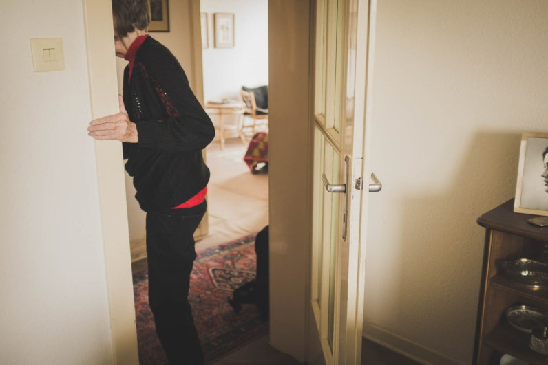 Helga leaving her living room. On the right hand side, there is a picture Nicoletta when she was 16 years old. Nicoletta grew up in this apartment with Helga and her grandmother Edith. Neuss, GERMANY, May 29, 2015.