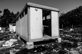 """A Roma child comes out of the toilet of the camp. May, 28 2015 Masseria del Pozzo in Giugliano-Naples Roma from the camp in Masseria del Pozzo in Giugliano (NA) live differently from other Roma camps in Italy. The municipality of Naples allowed them to live in an authorized area, within the Land of fires, surrounded by highly contaminated dumps. Giugliano, a town of about 120,000 inhabitants, is in fact the heart of the so-called """"Land of fires"""" is an area in Campania, situated between the province of Caserta and the province of Naples, sadly known for being the most polluted area of this region, due to millions of toxic waste that have been illegally dumped here over the past 20 years. Half of the Roma living here are children and they are totally abandoned to themselves, without either the possibility to attend school or have a proper health assistance. Their playground is the dump; they wander and play and spend their days between toxic miasmas and industrial waste. I came across the scene while having a tour of the surroundings of Giugliano. I didn't influence the scene in any way."""