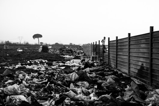 """A Roma child climbs over the steel fence around the camp. All around it, fields are full of waste. December, 15 2015 Masseria del Pozzo in Giugliano-Naples Roma from the camp in Masseria del Pozzo in Giugliano (NA) live differently from other Roma camps in Italy. The municipality of Naples allowed them to live in an authorized area, within the Land of fires, surrounded by highly contaminated dumps. Giugliano, a town of about 120,000 inhabitants, is in fact the heart of the so-called """"Land of fires"""" is an area in Campania, situated between the province of Caserta and the province of Naples, sadly known for being the most polluted area of this region, due to millions of toxic waste that have been illegally dumped here over the past 20 years. Half of the Roma living here are children and they are totally abandoned to themselves, without either the possibility to attend school or have a proper health assistance. Their playground is the dump; they wander and play and spend their days between toxic miasmas and industrial waste. I came across the scene while having a tour of the surroundings of Giugliano. I didn't influence the scene in any way."""