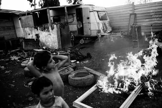 "Roma children set up fires. Though it's winter, they don't wear clothes. December, 15 2015 Masseria del Pozzo in Giugliano (NA) Roma from the camp in Masseria del Pozzo in Giugliano (NA) live differently from other Roma camps in Italy. The municipality of Naples allowed them to live in an authorized area, within the Land of fires, surrounded by highly contaminated dumps. Giugliano, a town of about 120,000 inhabitants, is in fact the heart of the so-called ""Land of fires"" is an area in Campania, situated between the province of Caserta and the province of Naples, sadly known for being the most polluted area of this region, due to millions of toxic waste that have been illegally dumped here over the past 20 years. Half of the Roma living here are children and they are totally abandoned to themselves, without either the possibility to attend school or have a proper health assistance. Their playground is the dump; they wander and play and spend their days between toxic miasmas and industrial waste. I came across the scene while having a tour of the surroundings of Giugliano. I didn't influence the scene in any way."