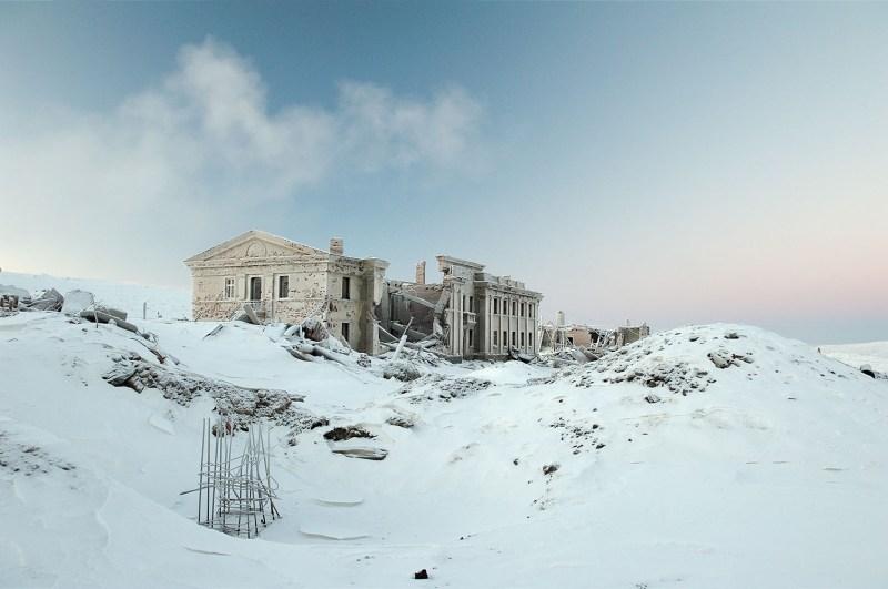 Déjà il y a 6 000 ans, les riches sous-sols de la région de Norilsk ont attiré les hommes, dont les traces de passage ont été relevées par des archéologues. Mais la réelle histoire de Norilsk commence au début du 20eme siècle, lorsque l'expédition du géologue Urvantsev mettra à jour les riches gisements de nickel, cuivre et cobalt. En 1936, l'URSS débute la construction du complexe métallurgique et de la ville. Ce travail difficile dans un environnement polaire est confié aux prisonniers du Goulag, travaillant dans des conditions inhumaines. Les mines, les usines de Nickel et de cuivre et une grande partie de la ville moderne ont été construites par les prisonniers. Pendant plus de 20 ans, 600 000 prisonniers – dont plusieurs milliers ont perdu la vie - auront travaillé à Norilsk, pour sa construction et son exploitation. Sur la photo – les ruines de la maison de la culture dans la cité « Medvejii Ruchei ». Cette cité était la première colonie de Norilsk, construite sur une partie du Goulag en 1956 juste à côté de la mine ouverte de « Medvejii ruchei ». Dans les années 90 elle fut fermée à cause des difficultés d'entretien et de la complexité de l'infrastructure. Ses habitants ont été déplacés dans de nouveaux quartiers d Norilsk.
