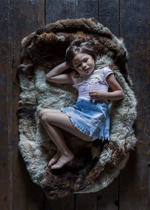 Five-year-old Irina poses on the old parka - hunting coat. As with many families in the village, she is a mixture of cultures and ethnicities: her mother is Tungus, and her father is Russian. Katangsky District, Irkutsky region. Russia, 2017