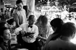 A man serves sparking wine inside a private party held by Neoenergia at the Sambódromo during carnival. February 2008.