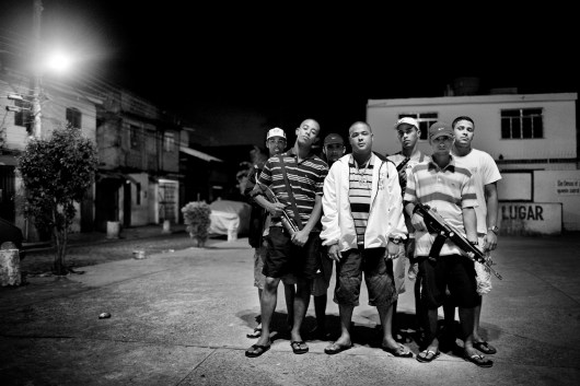 """Young men who belong to the """"Third Command"""" gang pose for a group portrait inside the Parque Royal favela on Governor's island in northern Rio de Janeiro. The man in the middle in a white coat is """"Vesguinho"""" the leader of the group. He was later killed by the military police in June 2009. July 2008."""