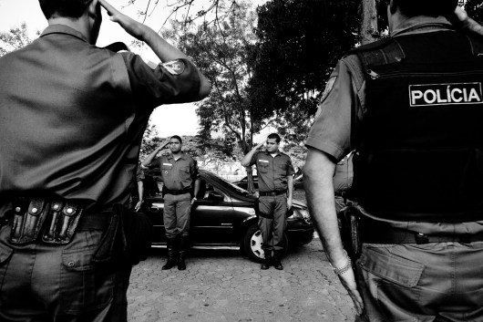 Military policemen line up while saluting the casket of Luiz Fernandes Marques da Silva, a military policeman murdered when he tried to stop a car robbery. July 2008.