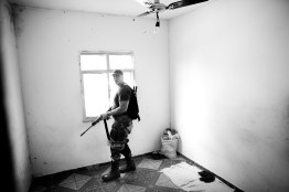 A DRAE agent patrolling from a window, during a police operation in the Mangueira favela to seize drugs and arrest traffickers. May 2009.