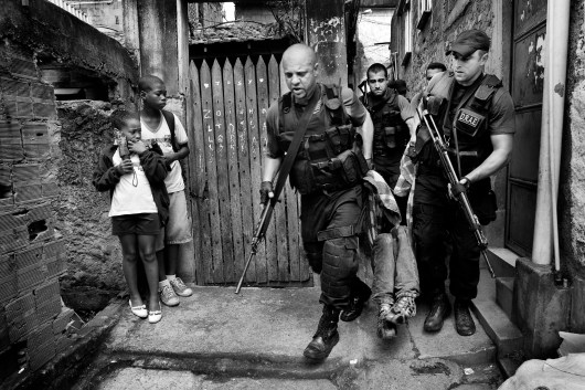 "Policemen from DRAE (Civilian Police division against weapons and explosives in Portuguese) carry the body of a young man, while two children coming back from school look at the scene. This is a case of ""resistance to authority."" After allegedly being told to stop by the police, the suspect ""resisted"" and was shot and taken to the hospital. In 2009 alone, the police officially killed 1049 people with this practice. November 2009."