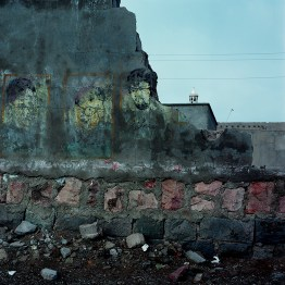 A broken wall with faded murals of martyrs from the Iran-Iraq war next to the Portogese castle on Hormuz island.