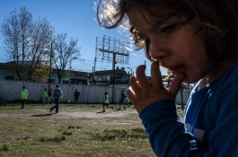 Buenos Aires, Isla Maciel. Children play football on a field in a sunny autumn day.