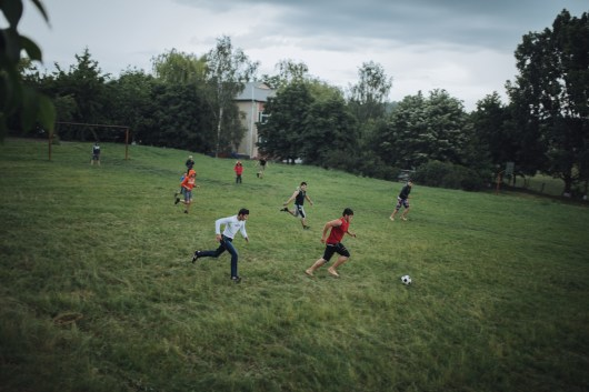 In spare time, mostly in the evenings, the guys get together to play football in the school yard.