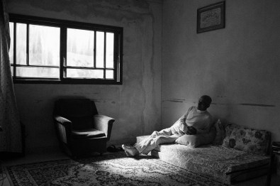 Khalil Zaanin is seen in his living room, in his home in Beit Hanoun, northern Gaza, Palestine, on Nov. 7th 2014. Khalil Zaanin's farm was hit several times by an F-16 missiles and bulldozed completely by the Israeli army, during the war in 2014. His water well was destroyed and it took him a month to repair it. His house, which is located directly at the Erez border crossing, the only border crossing with Israel, was partially ruined. Khalil says that it is a life of no guarantees what so ever, you cannot plan anything. In 2008 he decided not to invest in the house anymore, because during every conflict, the houses located at the buffer zone get affected.