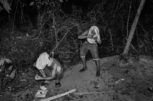MANAUS, BRAZIL - SEPTEMBER 01, 2015: Two drug dealers sniffing cocaine in the periphery of Manuas. Raul (on the left) was shot to death on April 2016 by a rival drug gang. The Amazonian capital of Manaus is currently in the midst of a violent drug war, with local gangs fighting for the control of the city's drug trade and violent gangsters killing each other over territory and drug debts as low as $2.