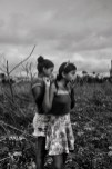 MANAUS, BRAZIL - OCTOBER 13, 2017: Two girls at the crime scene of an homicide in Manaus. The Brazilian Amazonian capital Manaus is currently experiencing massive homicide rates, five times higher than Sao Paulo's and up 168% in ten years, with local drug gang Familia Do Norte fighting a bloody turf war with the encroaching Primeiro Comando da Capital from Sao Paulo. Manaus is Brazil's closest big city to nearby drug production territories in Colombia and Peru which makes it a major transit point for Brazil (world's second largest cocaine consumer) and Europe, while in recent years, the city has also become a major consumption destination as the gangs flood the streets with Oxi, a cheap and destructive crack cocaine derivative.