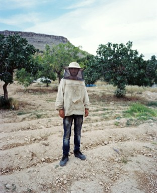 A beekeeper is standing by his beehives in a field near the town of Halfeti. The town of Halfeti partly flooded by the reservoir lake of the Birecik Dam on the Euphrates river.The dam was built on top of the ruins of the ancient city of Zeugma. The inhabitants of Halfeti and Savaçan were displaced to the city of Karaotlak (also called New Halfeti) built by the Housing Development Administration of Turkey. Halfeti,Turkey Halfeti, Turkey