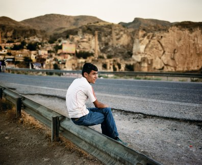 A man sits by the road facing a 12th century bridge leading to Hasankeyf over the Tigris River which will soon be flooded along with the town itself by the Ilisu Dam. Hasankeyf, Turkey.