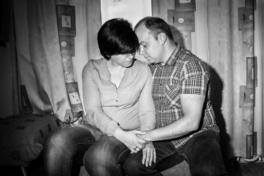 "Edita sits with her husband Darius in their living room. Editas father commited suicide January 2016. Europe. Lithuania, Kaunas, 21st of May 2016. Edita wrote:""I'm sitting exactly where I sat when I got your text and found out that you had killed yourself. This is the place where I sat, trembling and praying that this weren't true. I am sorry for not being an ideal daughter. I WANT you to know that I love you. I miss you dearly. Sometimes I still call your number and wait for your call on Sundays. Sometimes I curl into a ball and cry in my bed, because I miss you so much. Why did you tell me that you'll always stand by me? When you are gone, who should I go to? I remember you as I ride my bike – you gave me the freedom to ride it =) THANK YOU. I am happy, but I miss you so much. I no longer have a dad, and I'm angry at you. You left me. I love you and dream of you often. You are my daddy. Farewell. I love you."""