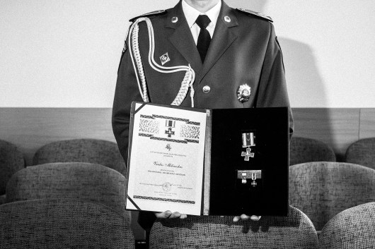 "Portrait of police officer Vaidas Miliauskas with his award certificate for saving a suicidal person. Europe, Lithuania, Prienai, 18th of May 2016. He wrote: ""A suicide person in an ambulance. I once saved a person who tried to take his own life by hanging himself. As we were on the way in an ambulance, together with the medic who oversaw him and his condition, he broke into violent resistance and started cursing us. They tend to have outbreaks of aggression, which would be difficult for the medic alone to subdue. This is why a officer is present at all times to oversee and, if needed, to physically restrain the person and protect not only him, but also medics from even worse outcomes. When I am off duty, resting, these faces appear not only in the form of dreams at night, but also during the day, quite unexpectedly. When these visions appear, I often think how he is doing, how his life goes and if he's happy. Sometimes I have the luck to see some of these people and inquire if everything is fine and if they are happy."""
