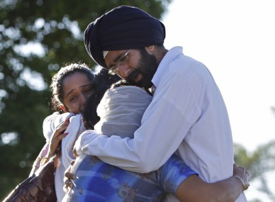 Aug. 6, 2012 - Oak Creek, Wisconsin, U.S. - KANWARDEEP SINGH KALEKA (R) hugs an unidentified woman while his sister SIMRAN KALEKA (L) hugs another unidentified relative on Monday as they meet and mourn the loss of their uncle Satwant Singh Kaleka, president of the Sikh temple, who died in Sunday's temple shootings in Oak Creek. (Credit Image: © Rick Wood/Milwaukee Journal Sentinel/MCT/ZUMAPRESS.com)