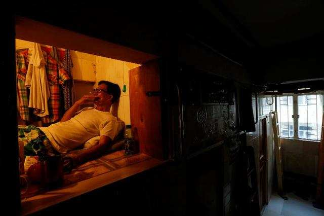 """Simon Wong, an unemployed 61-year-old man also living in Hong Kong, lives in a 4'x6' box. He's one of many residents living in so-called """"coffin homes."""""""