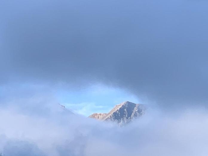 Mountaintop peeking through the clouds