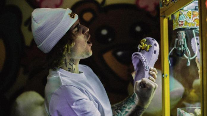Bieber at an arcade claw game cheering having won a shoe
