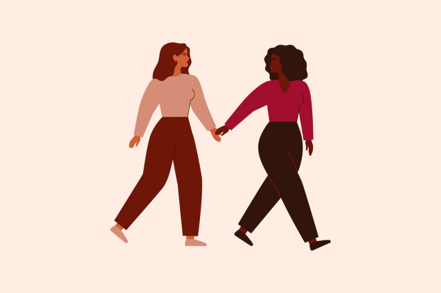 Two strong females walk together and hold arms. Black woman supports and leads her friend forward. Friendship, feminism movement and Sisterhood concept.