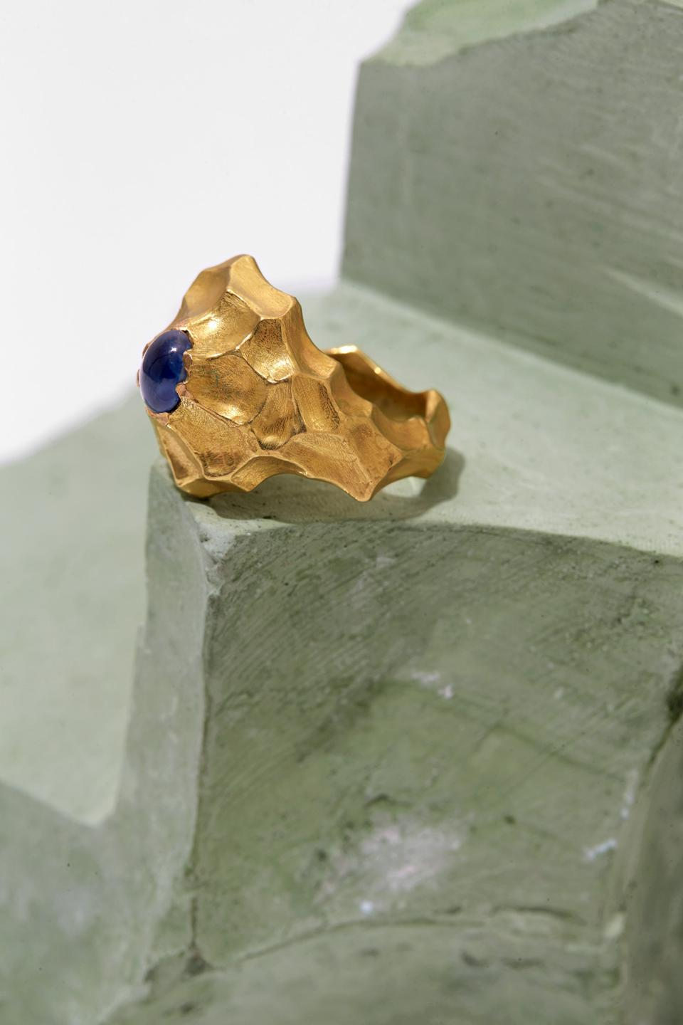An 18-karat gold and sapphire ring by Griegst is textured in a breaking wave pattern.