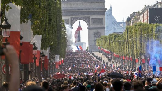 French fans attend the French football team parade on the Champs Elysees in a double-decker bus the day after their victory in the 2018 World Cup final, on July 16, 2018 in Paris, France. The French team won their second star after winning 4-2 against Croatia in the final.