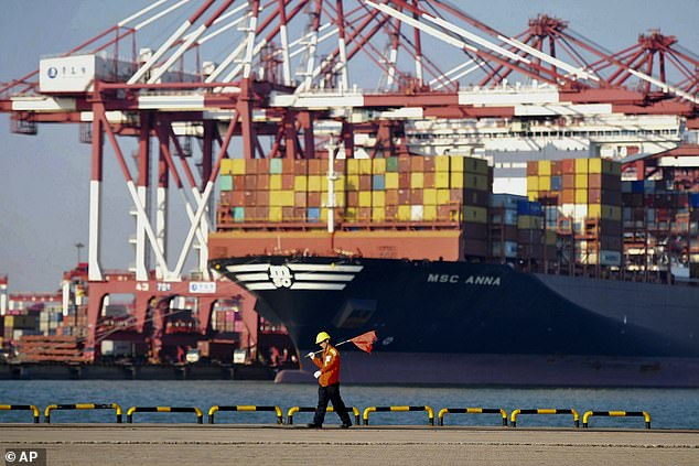 Aworker walks by the container ship docked at a port in Qingdao in China's Shandong province. Exports by China slumped 4.4% in December their biggest decline in two years