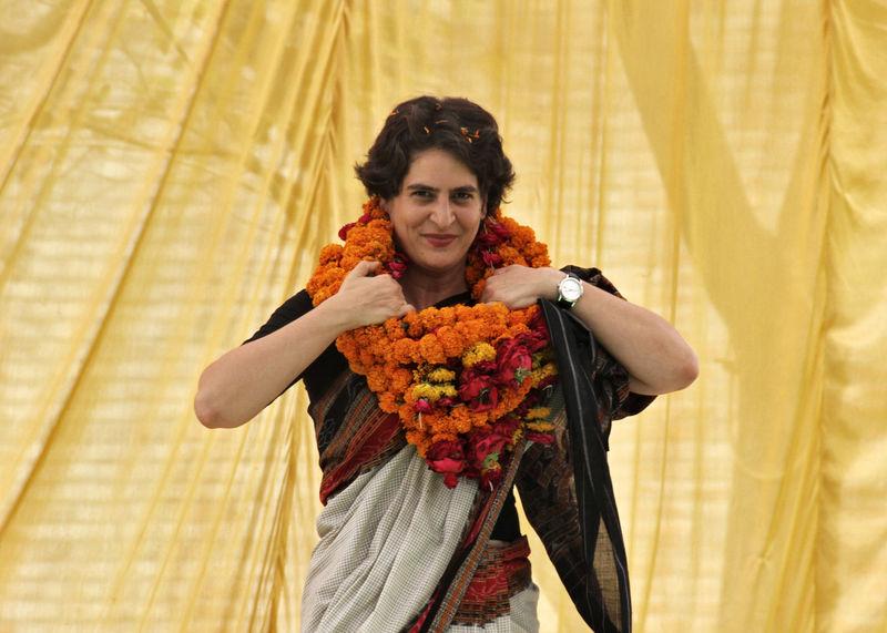 © Reuters. Priyanka Gandhi Vadra adjusts her flower garlands during an election meeting at Rae Bareli