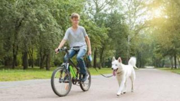 teen on bike with dog