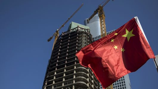 A Chinese national flag flies in front of a building under construction in the central business district of Beijing, China.