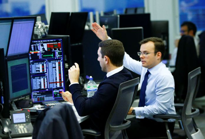 © Reuters. FILE PHOTO  - Traders work at their desks whilst screens show market data at CMC Markets in London