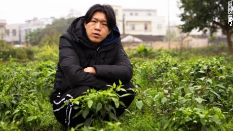 Wu Nengji poses on the rural pig farm from where he streams mini movies across China.