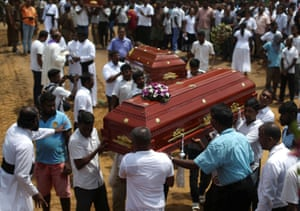 Coffins of victims are carried during a mass burial at a cemetery near St Sebastian church in Negombo.